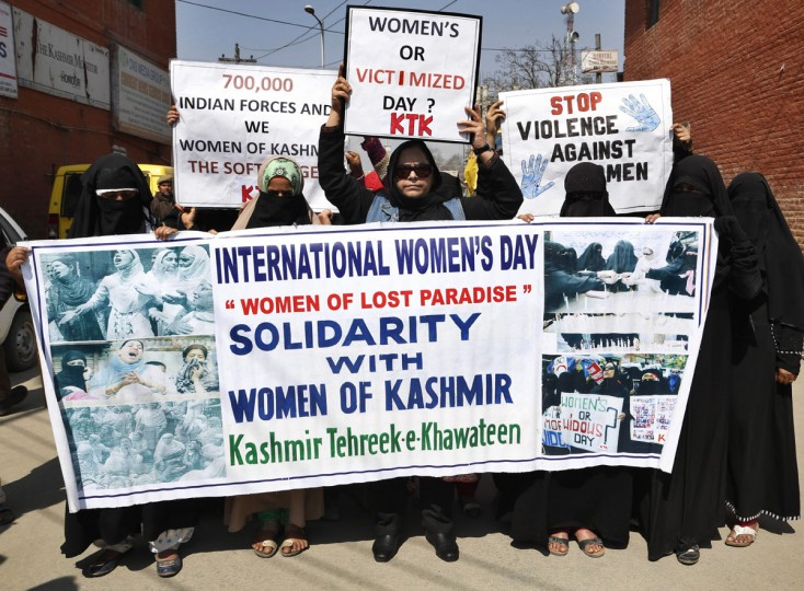 Activists of Kashmir Tehreek - e-Khawateen holds banner and placards during a demonstrate on International women's day in Srinagar, India, Tuesday, March 8, 2016. The protest was against the violence against women in the valley. (AP Photo/Mukhtar Khan)