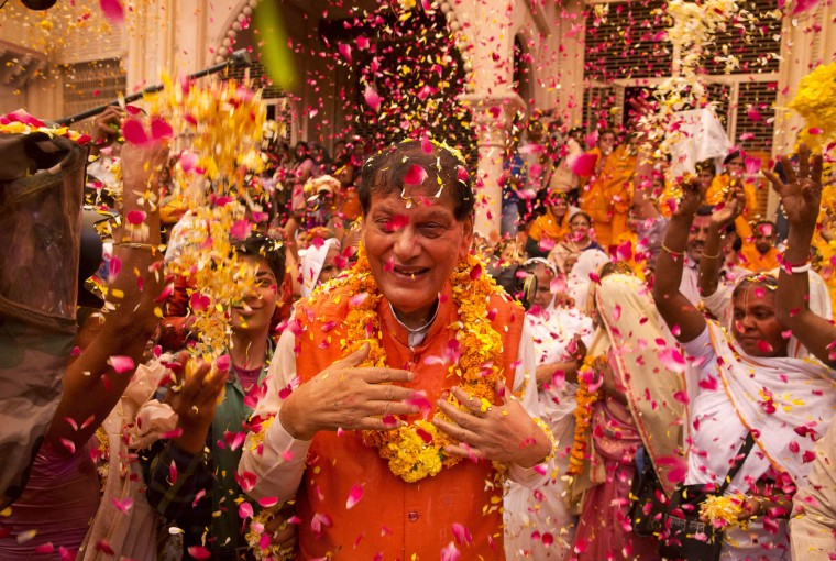 Indian Hindu widows throw colored powder and flower petals on Bindeshwar Pathak, founder of non-governmental organization Sulabh International, during Holi celebrations at the Gopinath temple, 180 kilometres (112 miles) south-east of New Delhi, India, Monday, March 21, 2016. A few years ago this joyful celebration was forbidden for Hindu widows. Like hundreds of thousands of observant Hindu women they would have been expected to live out their days in quiet worship, dressed only in white, their very presence being considered inauspicious for all religious festivities. (AP Photo/Manish Swarup)