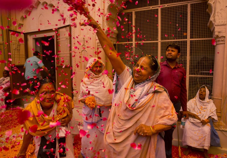 Indian Hindu widows throw flower petals during Holi celebrations at the Gopinath temple, 180 kilometres (112 miles) south-east of New Delhi, India, Monday, March 21, 2016. A few years ago this joyful celebration was forbidden for Hindu widows. Like hundreds of thousands of observant Hindu women they would have been expected to live out their days in quiet worship, dressed only in white, their very presence being considered inauspicious for all religious festivities. (AP Photo/Manish Swarup)