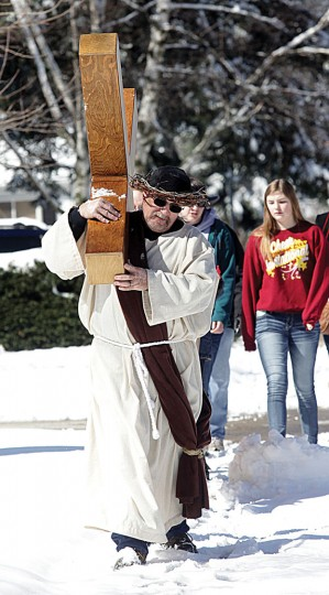 Ed Lombard, of Custer, Mich., carries a 20-pound wooden cross from Lake Michigan in Ludington, Mich., to Our Savior Lutheran Church near Scottville, Mich., on Good Friday, Friday, March 25, 2016. Lombard is hoping this event will energize people to find their faith. (Jeff Kiessel/Ludington Daily News via AP)