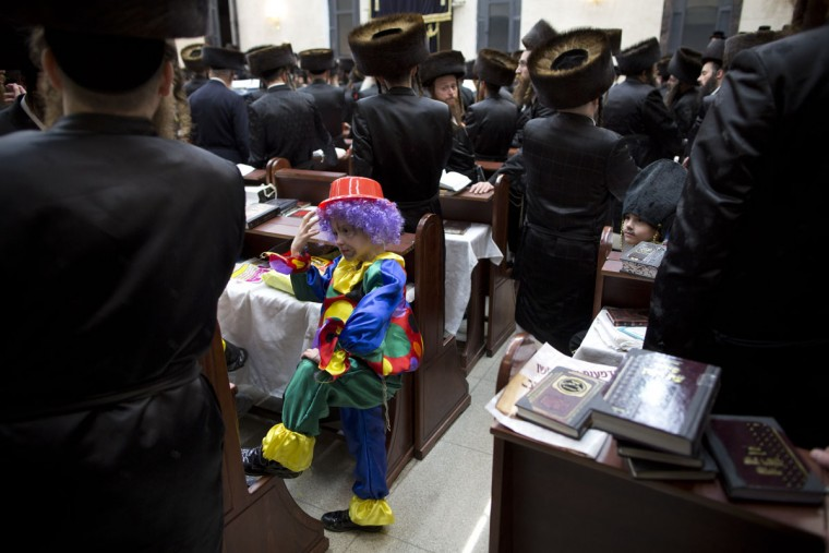 A Jewish Ultra-Orthodox boy wears a costume as others read the Book of Esther, which tells the story of the Jewish festival of Purim, in Bnei Brak, Israel, Wednesday, March 23, 2016. The Jewish holiday of Purim commemorates the Jews' salvation from genocide in ancient Persia, as recounted in the Book of Esther. (AP Photo/Oded Balilty)