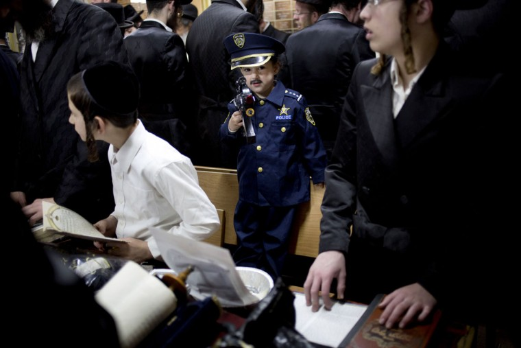Jewish Orthodox men and children of the Tzanz Hasidic dynasty community read the Book of Esther, which tells the story of the Jewish festival of Purim, in Netanya, Israel, Wednesday, March 23, 2016. The Jewish holiday of Purim commemorates the Jews' salvation from genocide in ancient Persia, as recounted in the Book of Esther. (AP Photo/Ariel Schalit)