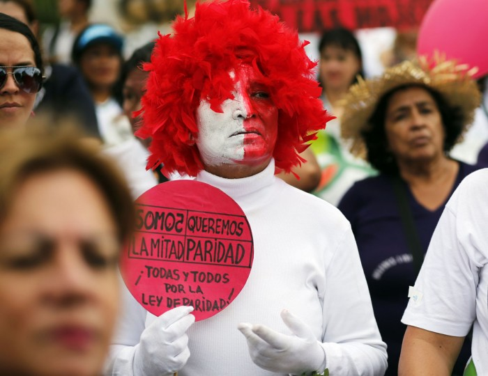 "A women holds a poster with a message that reads in Spanish, ""We are the other half, We want equality, all men , and all women for the Law of Equality,"" in front of the National Congress building, during a protest demanding a law for equality in political representation, marking International Women's Day in Asuncion, Paraguay, Tuesday, March 8, 2016. (AP Photo/Jorge Saenz)"