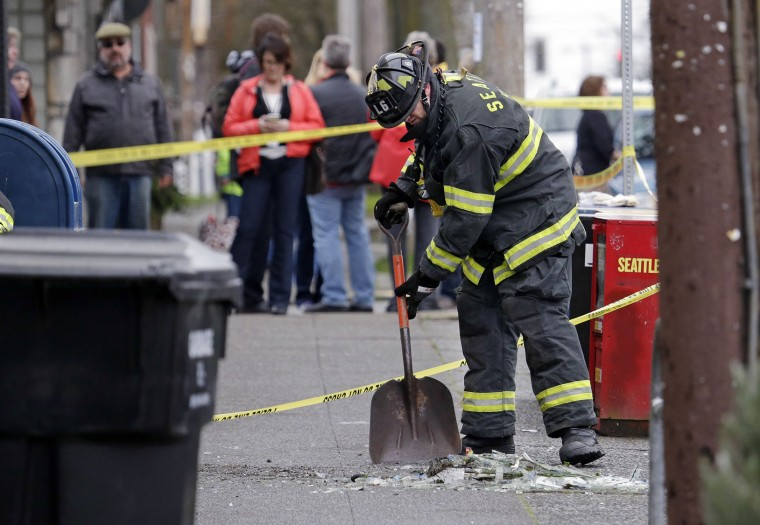 A firefighter cleans up plate glass from about a block away from the scene of an early morning explosion Wednesday, March 9, 2016, in Seattle. The natural gas explosion sent multiple firefighters to the hospital, none with serious injuries, and reduced several businesses to rubble. (AP Photo/Elaine Thompson)