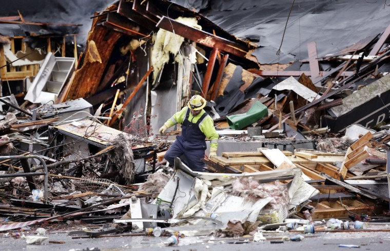 A worker walks in the rubble left from an early morning explosion Wednesday, March 9, 2016, in Seattle. The natural gas explosion sent multiple firefighters to the hospital, none with serious injuries, and reduced several businesses to rubble. (AP Photo/Elaine Thompson)