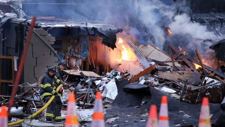 Firefighters move a hose into position as flames burn in the rubble left from an early morning explosion Wednesday, March 9, 2016, in Seattle. The explosion heavily damaged buildings and injured several firefighters. (AP Photo/Elaine Thompson)