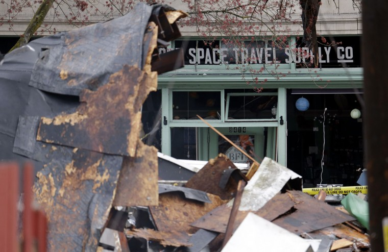 The Greenwood Space Travel Supply Co., which sells space-themed novelties and toys, is seen across the street from the rubble left from an early morning explosion Wednesday, March 9, 2016, in Seattle. The natural gas explosion sent multiple firefighters to the hospital, none with serious injuries, and reduced several businesses to rubble. (AP Photo/Elaine Thompson)
