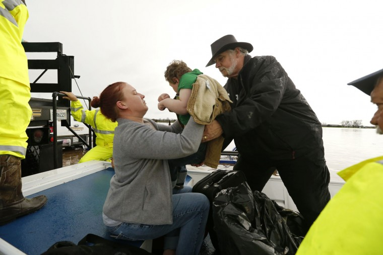 Sarah Yatcko, left, hands her son Tucker Neal to her father Jim Yatcko, as they are assisted by Bossier County Sheriff personnel from a boat to a high water vehicle while being evacuated from their home during rising floodwaters in Bossier Parish, La., Thursday, March 10, 2016. (AP Photo/Gerald Herbert)