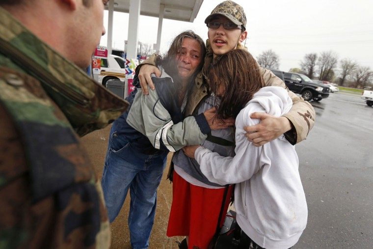 Dacia Winters, let, hugs Ryan Ficca, center, and Stormy Winters after they were evacuated in a Louisiana National Guard high water vehicle from rising floodwaters in Bossier Parish, La., Thursday, March 10, 2016. Heavy rain has forced evacuations and caused flash flooding for more than a day. (AP Photo/Gerald Herbert)