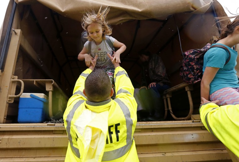 Bossier Parish Sheriff personnel help Christine Sizemore, 6, out of a high water vehicle after she was evacuated from rising floodwaters in Bossier Parish, La., Thursday, March 10, 2016. Heavy rain has forced evacuations and caused flash flooding for more than a day. AP Photo/Gerald Herbert)