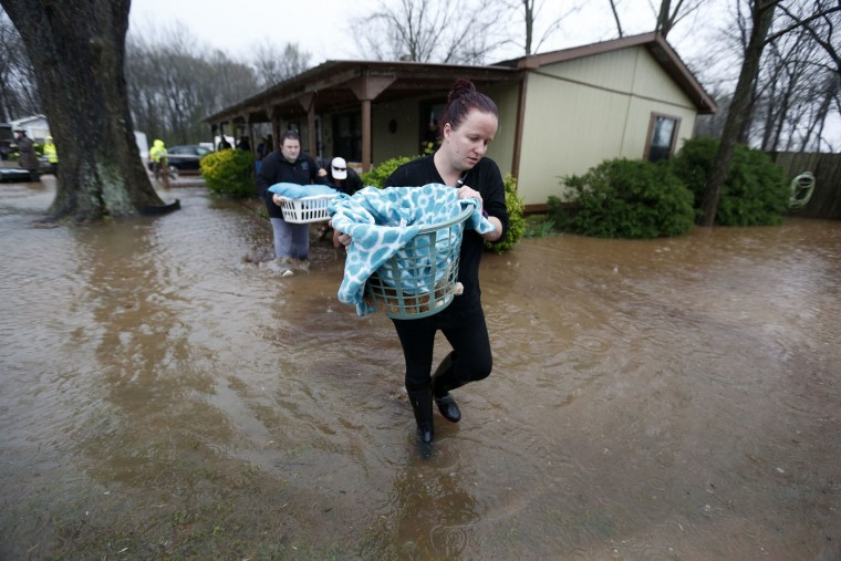 Camie Kelly walks through floodwaters as she carries her family cat from the the Pecan Valley Estates trailer park as residents evacuate due to rising water in Bossier City, La., Wednesday, March 9, 2016. (AP Photo/Gerald Herbert)