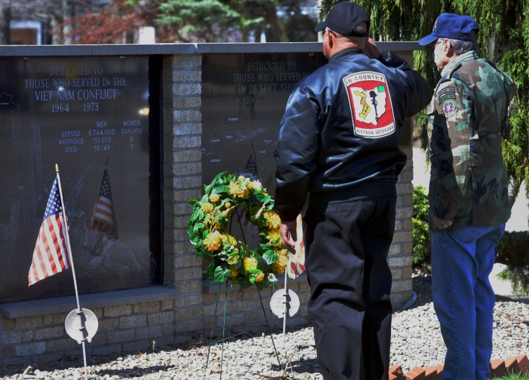 Richard Trask, right, and Charles McQueen salute after placing a wreath at the Ashtabula Vietnam War Memorial during a ceremony commemorating the 50th anniversary of the Vietnam War, in Ashtabula, Ohio, Tuesday, March 29, 2016. The U.S. Department of Veterans Affairs has announced it will conduct events at VA facilities across the nation on March 29 to recognize, honor and thank Vietnam veterans and their families for their service as part of the national Vietnam War Commemoration. (Warren Dillaway/The Star-Beacon via AP)