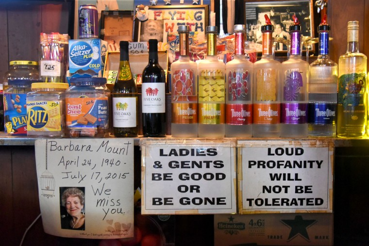 A memorial sign for a popular barmaid, Barbara Mount, who died in 2015, is posted behind the bar with other friendly cautions for the customers. (Amy Davis/Baltimore Sun)