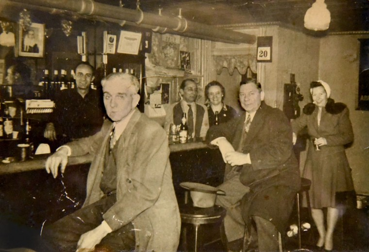 The owners, Frank DeSantis Sr. and Mary Victoria DeSantis stand behind the bar at center, and pose for this undated snapshot with their son, Alfred, the bartender at left, and some customers. (Courtesy of Dominic DeSantis)