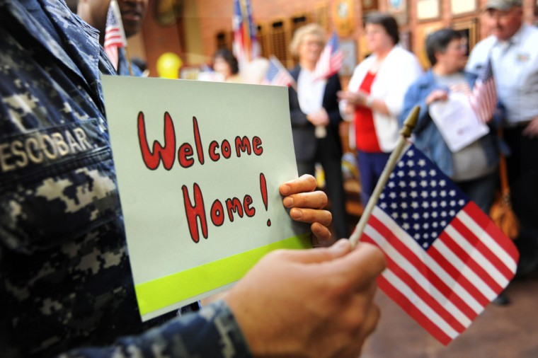 """AZ2 Guilermo Escobar holds a Welcome Home sign for Vietnam Veterans."""" A """"Welcome Home"""" parade and private ceremony is held at the Charlotte Hall Veterans Home. About 170 of the nearly 300 residents of this assisted-living facility are Vietnam vets. (Photo by Algerina Perna/Baltimore Sun Staff)"""