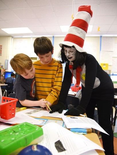 The Cat in the Hat, filling in for second grade teacher Mrs. Lisa Ferrer, helps students Jack Boivin, 7, left, and Kieran Pendergraph, 8, center, at Hillsmere Elementary School. To celebrate Dr. Seuss's 112th birthday, schools and libraries across the country took part in the annual Read Across America Day, dressing like Seuss's characters and reading both is works and other favorite children's books.