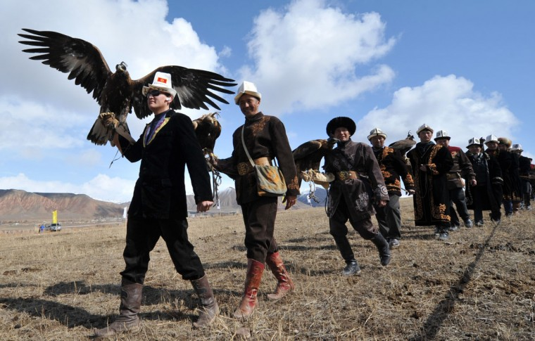 "Kyrgyz berkutchi (eagle hunters) carry their birds, golden eagles, during the hunting festival ""Salburun"" in the village of Alysh, near Naryn, 350 km outside Bishkek, on March 13, 2016. (VYACHESLAV OSELEDKO/AFP/Getty Images)"