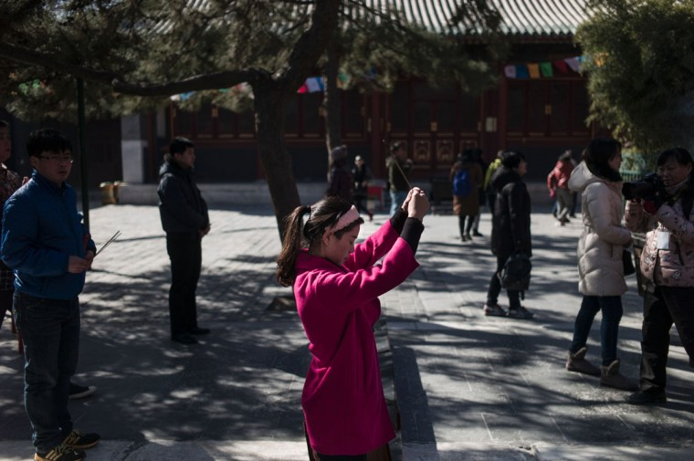 A woman holds incense sticks as she prays during the Beating Ghost festival at the Yonghe Temple, also known as the Lama Temple, in Beijing on March 8, 2016. The Beating Ghost festival, or Da Gui festival in Chinese, is an important ritual of Tibetan Buddhism and is believed to expel evil spirits and shake off troubles. (FRED DUFOUR/AFP/Getty Images)