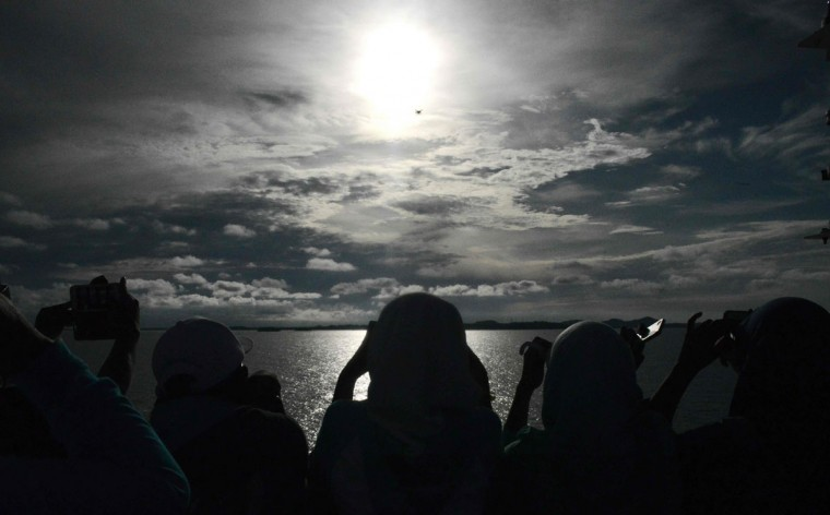 Passengers gather to watch the total solar eclipse onboard the Indonesian cruise ship KM Kelud near the island of Belitung in Indonesia on March 9, 2016. (GOH CHAI HIN/AFP/Getty Images)