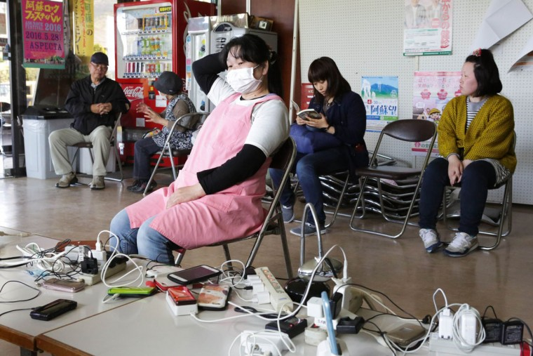 KUMAMOTO, JAPAN - APRIL 17: Local residents rest while charging their cellphones after evacuating from their houses on April 17, 2016 in Minamiaso, Kumamoto. A magnitude-7.3 earthquake hit Kumamoto prefecture on Japan's Kyushu Island on Saturday after one measuring 6.4 struck on Thursday. As of Sunday, reports indicate that 42 people have been killed, 1,500 were injured, and 11 people remain missing. An estimated 80,000 homes are without power and 400,000 homes have no running water. (Photo by Taro Karibe/Getty Images)