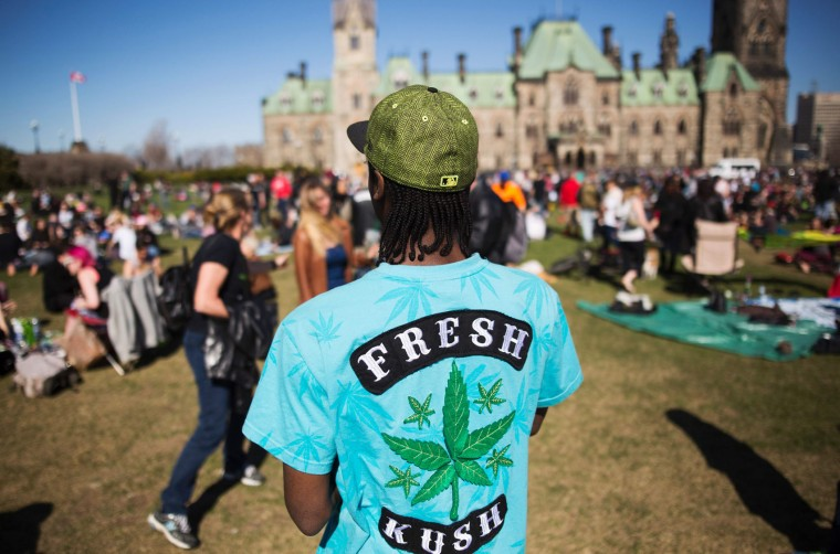 A man look on as people gather to celebrate National Marijuana Day on Parliament Hill in Ottawa, Canada on April 20, 2016. Canada will take steps next year to legalize marijuana, Health Minister Jane Philpott announced. Philpott offered several reasons for ending the ban on pot, including the view that laws in Canada and abroad criminalizing marijuana use have been both overly-harsh and ineffective. (Chris Roussakis/AFP/Getty Images)
