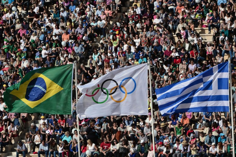 A picture taken on April 27, 2016 shows Brazilian, Olympic and Greek flags as spectators attend the handover ceremony of the Olympic flame at the Panathinean stadium in Athens. Greece on April 27 handed over to Brazilian officials the Olympic flame of the Rio Games as the 100-day countdown to the August 5 opening ceremony begins. (AFP Photo/Louisa Gouliamaki)