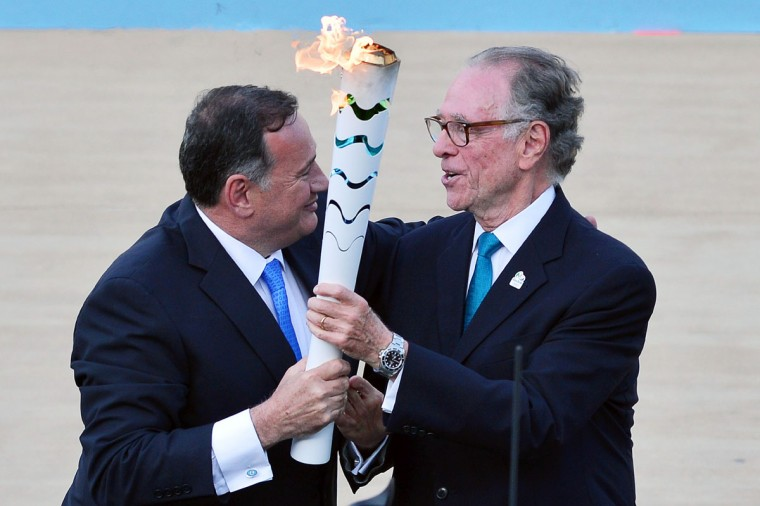 President of the Hellenic Olympic Committee Spyros Kapralos (L) passes the Olympic flame torch to Rio 2016 organising committee president Carlos Nuzman during the handover ceremony at Panathinean stadium in Athens, on April 27, 2016. Greece on April 27 handed over to Brazilian officials the Olympic flame of the Rio Games as the 100-day countdown to the August 5 opening ceremony begins. (AFP Photo/Louisa Gouliamaki)