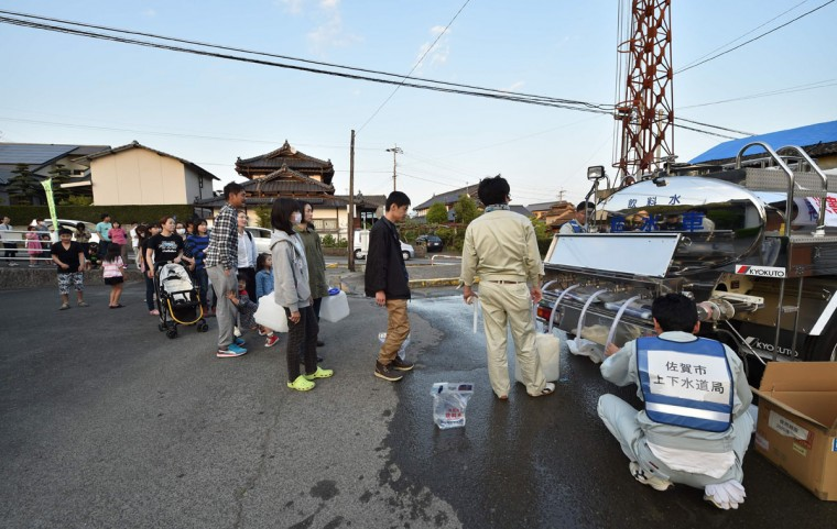 People queue for water supplies in Higashi-ku, Kumamoto City on April 15, 2016, after a 6.5-magnitude quake struck the southwestern island of Kyushu on April 14. Rescuers searched through rubble for possible survivors on April 15 after a powerful earthquake in southern Japan left at least nine people dead and hundreds injured, though officials said the toll was unlikely to rise dramatically. / AFP PHOTO / KAZUHIRO NOGIKAZUHIRO NOGI/AFP/Getty Images