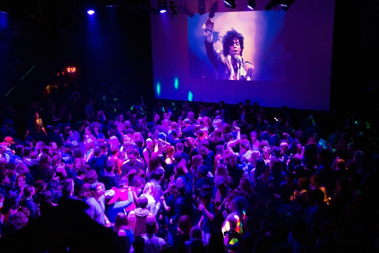Guests dance to Prince music as a slide show flashes images of the artist above the stage during a memorial dance party at the First Avenue nightclub on April 21, 2016 in Minneapolis, Minnesota. Prince, 57, was pronounced dead shortly after being found unresponsive at Paisley Park Studios in Chanhassen, Minnesota near Minneapolis. (Photo by Scott Olson/Getty Images)