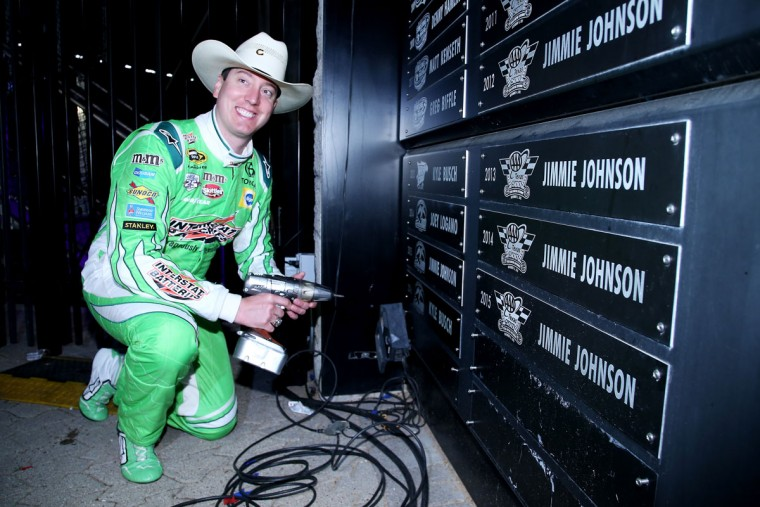 FORT WORTH, TEXAS - APRIL 09: Kyle Busch, driver of the #18 Interstate Batteries Toyota, affixes a plaque inscribed with his name after winning the NASCAR Sprint Cup Series Duck Commander 500 at Texas Motor Speedway on April 9, 2016 in Fort Worth, Texas. (Photo by Sean Gardner/Getty Images)