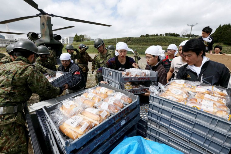 Soldiers of the Ground Self-Defence Force (GSDF) and students of Tokai University carry relief food transported by helicopters of the GSDF at the isolated university campus after earthquakes in Minami-Aso, Kumamoto prefecture, on April 17, 2016. At least 41 people are known to have died in the double disaster, with up to eight still missing -- feared buried in shattered houses or under torrents of mud. AFP PHOTO