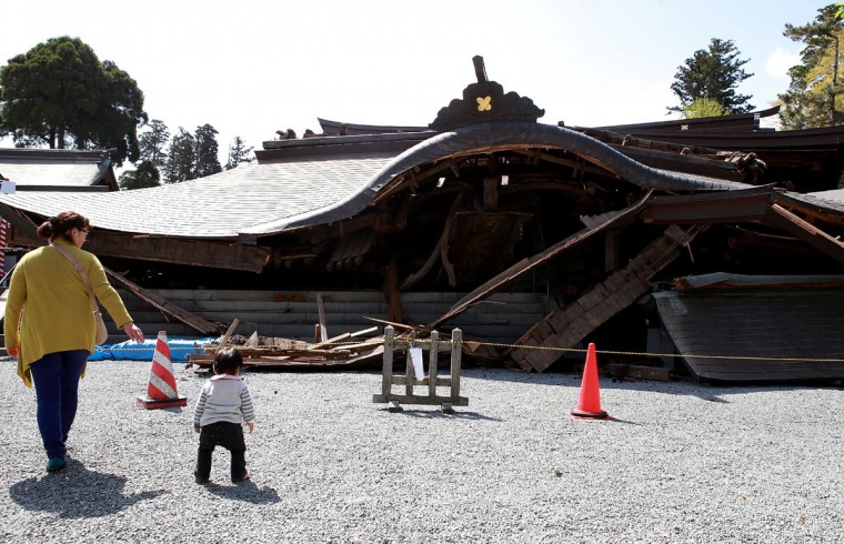 Local residents walk past the 250-year-old two-storey main gate of Aso Shrine which collapsed after the recent earthquakes in Aso, Kumamoto prefecture, on April 17, 2016. The US military was set to join Japanese rescuers on April 17 racing against the threat of more landslides to reach people still trapped by two big earthquakes which had killed at least 41 people. / AFP PHOTO / JIJI PRESS / STR / Japan OUTSTR/AFP/Getty Images