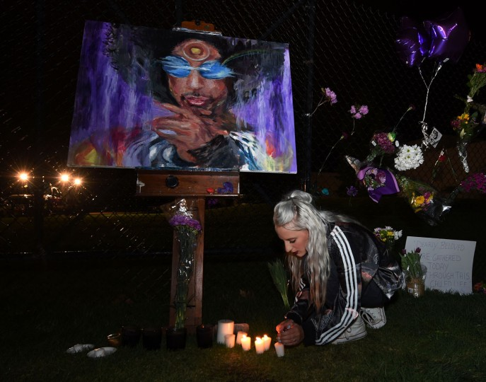 Fans light candles outside the Paisley Park residential compound of music legend Prince in Minneapolis, Minnesota, on April 21, 2016. Emergency personnel tried and failed to revive music legend Prince, who died April 21, 2016, at age 57, after finding him slumped unresponsive in an elevator at his Paisley Park studios in Minnesota, the local sheriff said. (Mark Ralston/AFP/Getty Images)