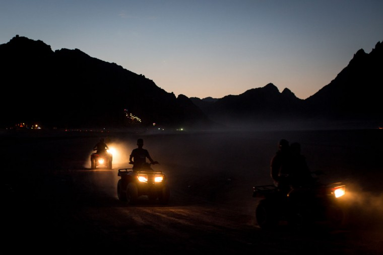 Tourists enjoy a sunset quad bike tour on April 2, 2016 in Sharm El Sheikh, Egypt. Prior to the Arab Spring in 2011 some 15million tourists would visit Egypt each year. The resort town of Sharm El Sheikh was built around tourism however tourist numbers have plummeted after recent terrorist attacks with flights from major UK carriers being suspended and foreign offices around the world warning citizens of the 'High threat from terrorism' Sharm El Sheikh is almost a ghost town, with many resorts being abandoned and business forced to close. (Photo by Chris McGrath/Getty Images)