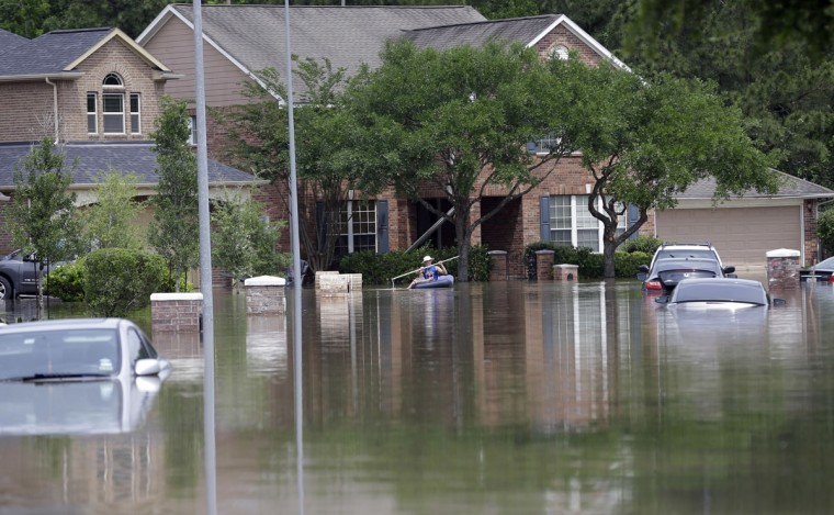 A person paddles through a flooded neighborhood, Tuesday, April 19, 2016, in Spring, Texas. Storms have dumped more than a foot of rain in the Houston area, flooding dozens of neighborhoods. (AP Photo/David J. Phillip)
