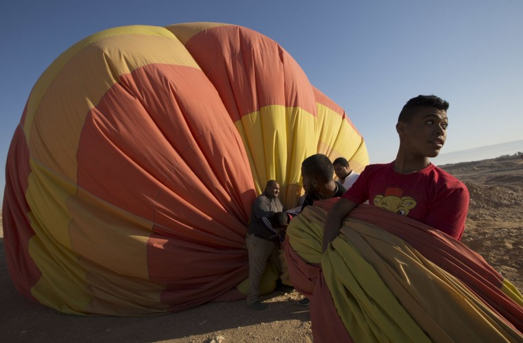 In this picture taken from a balloon Friday, April 1, 2016, ground crew members collect a hot air balloon after a tour over the west bank of the Nile River, in Luxor, Egypt. They take off at first light, reinforced wicker baskets filled with people, heading into the skies over Luxor, Egypt. The ride lasts about 20 minutes, before the pilot begins looking for a safe landing zone. Tourists brace themselves for landing, a usually bumpy affair more akin to a soft crash landing. (AP Photo/Amr Nabil)