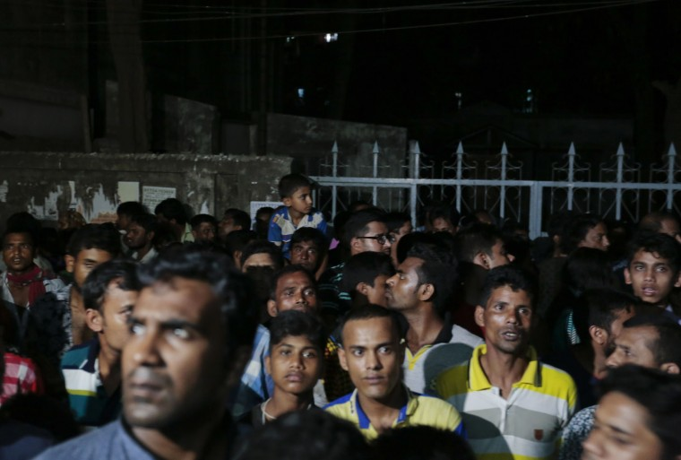 Bangladeshi people gather outside a building where two people were found stabbed to death in Dhaka, Bangladesh, Monday, April 25, 2016. Police in Bangladesh say unidentified assailants have stabbed two men to death, including a gay rights activist who also worked for the U.S. Agency for International Development. (AP Photo/A.M.Ahad)
