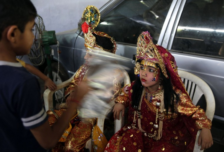 An Indian boy fans his friends dressed as Hindu God Ram and Sita, right, before the start of a procession to celebrate the Ram Navami festival in Allahabad,India , Friday, April 15, 2016. Hindu devotees celebrate the festival of Ram Navami, the birth anniversary of Lord Rama, which also marks the end of the nine-day long fasting and Navaratri festival. (AP Photo/Rajesh Kumar Singh)