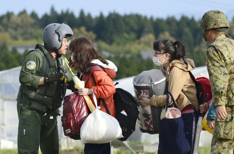 College students with their belongings wait for the arrival of a helicopter of the Japan Self-Defense Forces to be transferred to safer place in Minamiaso village, Kumamoto prefecture, Japan, Saturday, April 16, 2016. The powerful earthquake struck southwestern Japan early Saturday, barely 24 hours after a smaller quake hit the same region. (Hiroko Harima/Kyodo News via AP)