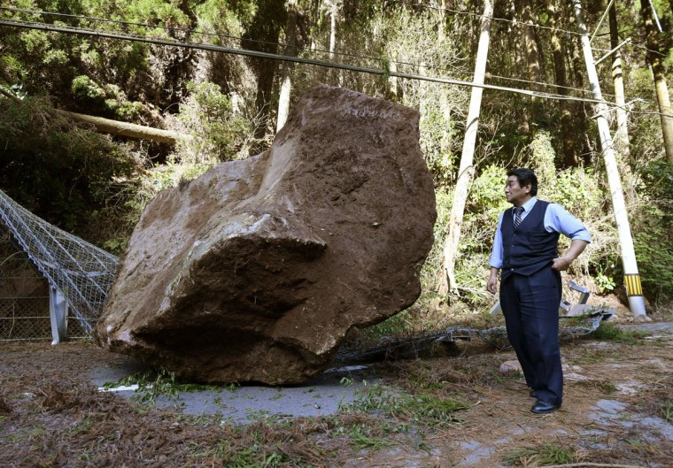 A big stone sits on a road after it fell off and broke the fence, following the earthquake in Kikuchi city, Kumamoto prefecture, southern Japan Saturday, April 16, 2016. A powerful earthquake struck southern Japan early Saturday, barely 24 hours after a smaller quake hit the same region.(Kyodo News via AP)