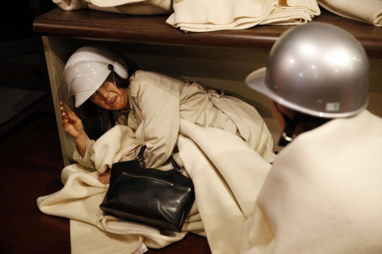 A hotel guest tries to protect herself from repeated aftershocks in Kumamoto, southern Japan early Saturday, April 16, 2016. A powerful earthquake struck southern Japan early Saturday, barely 24 hours after a smaller quake hit the same region. (Shohei Miyano/Kyodo News via AP)