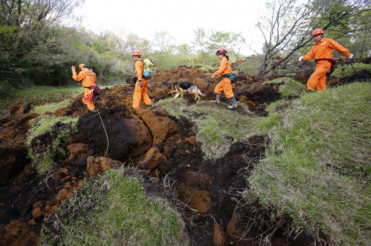 Rescuers and a search dog check the damage around a landslide area caused by earthquakes in Minamiaso, Kumamoto prefecture, Japan, Sunday, April 17, 2016. Two nights of increasingly terrifying earthquakes flattened houses and triggered major landslides in southern Japan. (AP Photo/Shizuo Kambayashi)