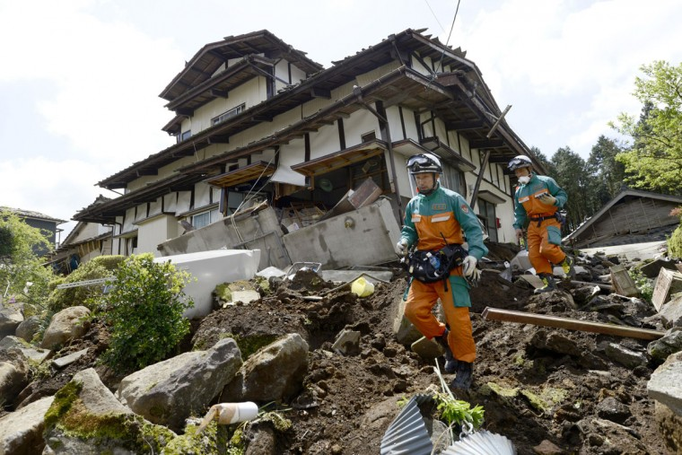 Rescuers check the damage around a landslide area caused by earthquakes in Minamiaso, Kumamoto prefecture, Japan, Sunday, April 17, 2016. Two nights of increasingly terrifying earthquakes flattened houses and triggered major landslides in southern Japan. (Koji Harada/Kyodo News via AP)