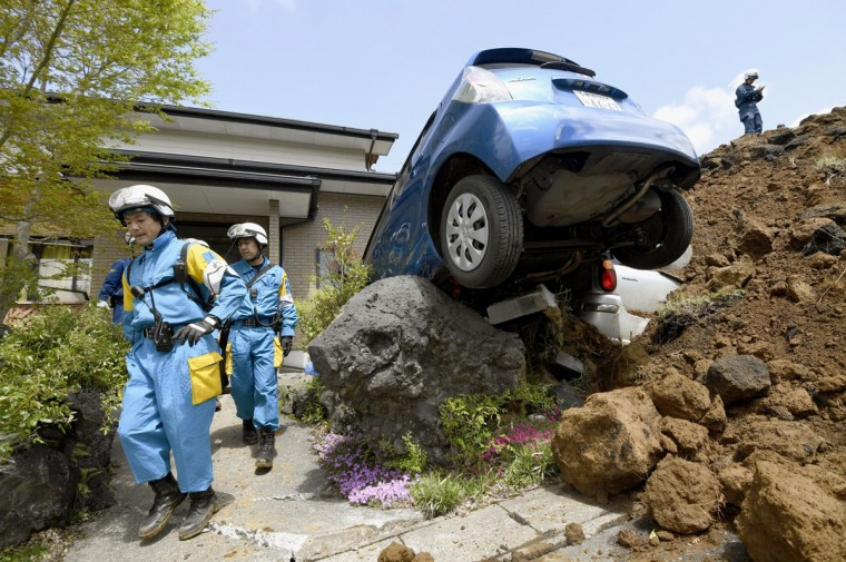 Police officers conduct a search operation at the site of a landslide caused by an earthquake in Minamiaso, Kumamoto prefecture, Japan, Sunday, April 17, 2016. Two nights of increasingly terrifying earthquakes flattened houses and triggered major landslides in southern Japan. (Yohei Fukai/Kyodo News via AP)