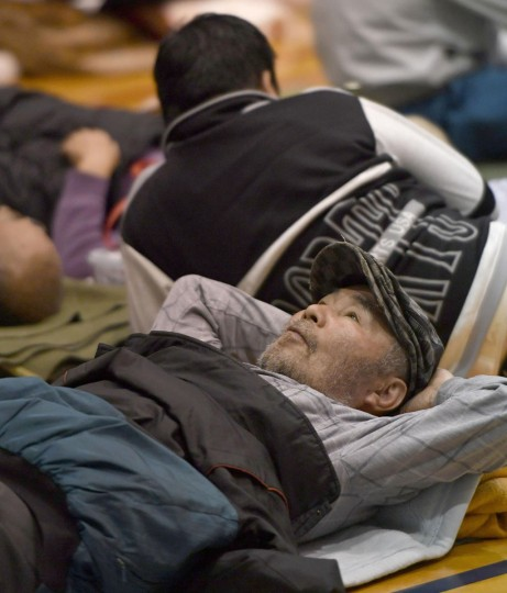 An evacuee takes a rest at a gym-turned shelter after an earthquake in Nishihara village, Kumamoto prefecture, Japan, Saturday, April 16, 2016. Powerful earthquakes a day apart shook southwestern Japan, trapping many others beneath flattened homes and sending thousands of residents to seek refuge in gymnasiums and hotel lobbies. (Yohei Nishimura/Kyodo News via AP)