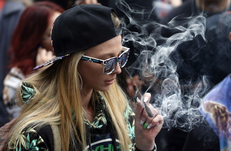 A woman smokes marijuana during the annual 4/20 marijuana gathering at Civic Center Park in downtown Denver, Wednesday, April 20, 2016. Public consumption remains illegal under the state's recreational pot law, which was passed in 2012. Fans of the drug have long marked April 20 as a day to enjoy pot — especially at 4:20 p.m. — and to call for increased legal access to it. (AP Photo/Brennan Linsley)