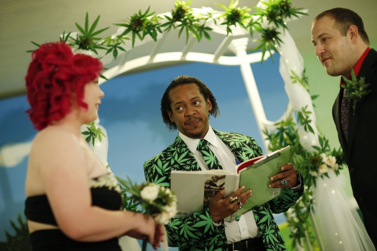 Natalie Rice, left, and Lee Rice, right, are married by Locq Fortune beneath a canopy of faux marijuana plants during a ceremony at the Cannabis Chapel, Wednesday, April 20, 2016, in Las Vegas. Natalie and Lee Rice were the first couple to marry at the marijuana themed wedding chapel, which opened Wednesday. (AP Photo/John Locher)