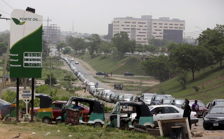 Cars queue to buy fuel at a petrol station in Abuja, Nigeria, Friday, April 1, 2016. Nigeria's oil minister apologized this week for a fuel shortage that has created long lines at gas stations and left travelers stranded on highways in sub-Saharan Africa's top oil producing country. (AP Photo/Sunday Alamba)