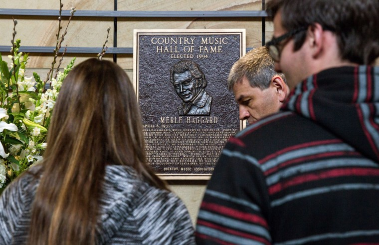 """Visitors pay their condolences at the plaque of Merle Haggard at the Country Music Hall of Fame in Nashville, Tenn., on Wednesday, April 6, 2016. Haggard, who rose from poverty and prison to international fame through his songs about outlaws, underdogs and an abiding sense of national pride in such hits as """"Okie From Muskogee"""" and """"Sing Me Back Home,"""" died Wednesday at 79, on his birthday. (AP Photo/Erik Schelzig)"""