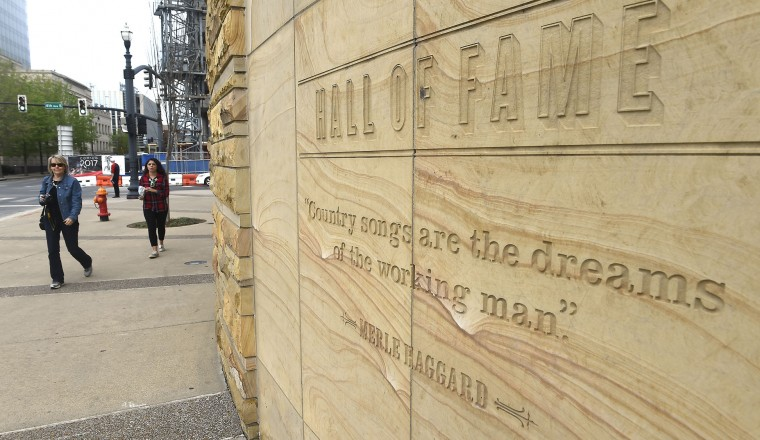 """Fans walk past a quote by Merle Haggard engraved on the outside the Country Music Hall of Fame, Wednesday April 6, 2016, in Nashville, Tenn., after learning of his death. Haggard, who rose from poverty and prison to international fame through his songs about outlaws, underdogs and an abiding sense of national pride in such hits as """"Okie From Muskogee"""" and """"Sing Me Back Home,"""" died Wednesday at 79, on his birthday. (Larry McCormack/The Tennessean via AP)"""